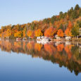 Brilliant fall colors reflected in a smooth, calm lake.  Photographed in morning light.